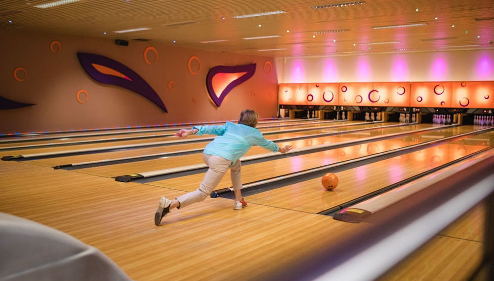 One senior woman bowling with her friends. She has just thrown the ball.