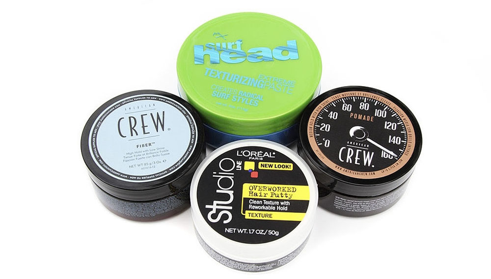 """West Palm Beach, USA - October 14, 2012: A group of four different men's hair styling pastes or pomades. Brands include Loreal Studio Line, American Crew Pomade, American Crew Fiber, and FX Surf Head."""